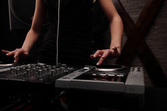 Closeup hands. woman in black dj with white headphones playing music on mixer with light beam effects. Young woman dj in headphones playing music on mixer on Stock Photo