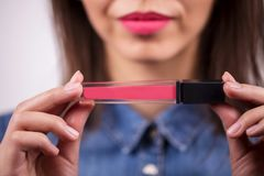 Closeup on the hands of women pink lip gloss, lipstick. Cosmetics, makeup concepts. stock photography