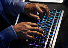Closeup of hands working on computer keyboard stock photography