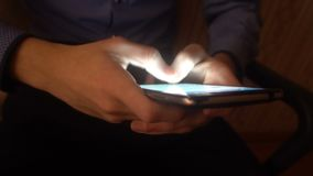 Closeup of hands of a young man flipping through the news on the smartphone stock video