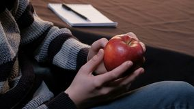 Closeup of the hands of a young man in a gray sweater. The guy is considering a ripe red apple. Student, artist or writer. Noteboo