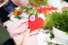 Closeup of hands of young woman florist creating heart shape with flowers bouquet on the table royalty free stock photography