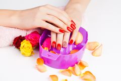 Girl with bright red polish on the nails in salon Stock Photos