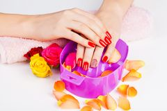 Girl with bright red polish on the nails in salon Stock Image