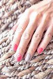 Closeup of hands of a young woman with red manicure on nails against wooden background. royalty free stock photo