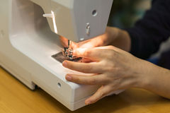 Closeup of hands a young woman spends thread a sewing machine at Royalty Free Stock Photo