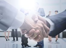 Concept of assistance in drafting business - friendly handshake. Closeup of handshake of businessmen on background of employees Stock Photos