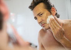 Closeup of a handsome man shaving his beard. Mature handsome man shaving in front of mirror Royalty Free Stock Photography