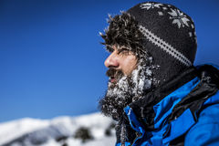 Closeup of  handsome man with snow on his beard wearing winter h Royalty Free Stock Photos