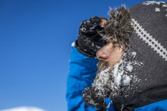 Closeup of  handsome man with snow on his beard wearing winter h Royalty Free Stock Photography