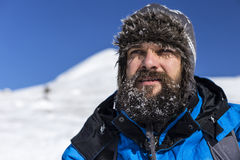 Closeup of  handsome man with snow on his beard wearing winter h Stock Image