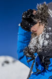 Closeup of  handsome man with snow on his beard wearing winter h Stock Photos