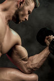 Closeup of a handsome power athletic man bodybuilder doing exercises with dumbbell. Fitness muscular body on dark. Background. Selective Focus. Awesome Stock Photo