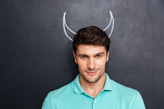 Closeup of handsome young man with drawn devil horns. Over blackboard background Royalty Free Stock Photography