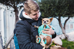 Closeup of handsome young man holding a cute chihuahua dog outdoor.  Royalty Free Stock Images