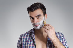 Closeup of handsome young man putting shaving foam Stock Photo