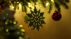 Closeup of hanging Christmas Tree ornaments. A close up shot of a 30+ year old artificial christmas pine tree with white and red LED lights on it and hanging Royalty Free Stock Photo