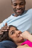 Closeup on happy African American woman lying on man legs. Stock Image