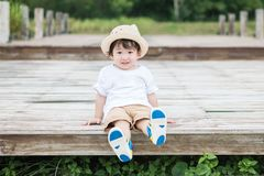 Closeup happy asian kid with smile face sit at wood pathway in the park background stock image