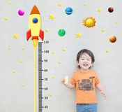 Closeup happy asian kid stand for measure height with cute cartoon at the marble stone wall textured background in growth of kid c. Closeup happy kid stand for stock photos