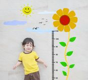 Closeup happy asian kid stand for measure height with cute cartoon sunflower at the marble stone wall textured background Royalty Free Stock Image