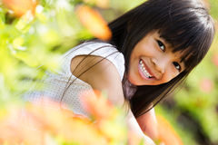 Closeup happy asian little girl sitting on flower field. Outdoor portrait Royalty Free Stock Image
