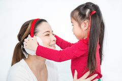 Closeup happy Asian mother and baby girl using red headphones royalty free stock images