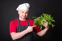 Closeup of happy chef holding arugula beam royalty free stock photos