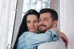 A closeup of a happy couple hugging and kissing in the bedroom royalty free stock images