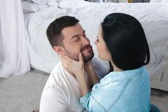A closeup of a happy couple hugging and kissing in the bedroom stock image