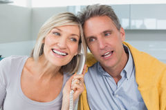 Closeup of a happy couple using telephone in kitchen Royalty Free Stock Photography