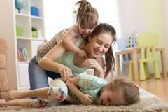 Closeup of happy family. Joyful mom and her kids having a fun pastime on floor in living room. Closeup of happy family. Joyful mom and her children having a fun Stock Image