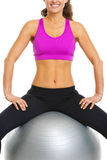 Closeup on happy fitness young woman sitting on fitness ball Royalty Free Stock Photography