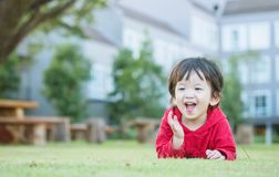 Closeup happy asian kid lied on grass floor in the garden background with cute motion Royalty Free Stock Photos