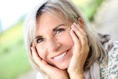 Closeup of happy mature woman with hands under chin Royalty Free Stock Images