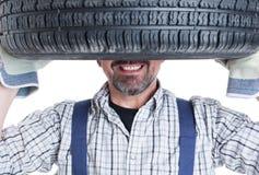 Closeup of happy mechanic holding wheel on head Royalty Free Stock Photography