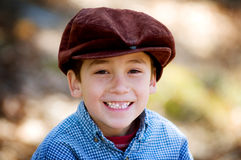 Closeup of a happy smiling little boy in a cap. Six year old boy smiling and wearing a newsboy cap Stock Photography