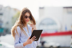 Closeup of happy successful businesswoman in sunglasses using tablet pc. Royalty Free Stock Photography