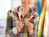 Closeup on happy tailor woman showing scissors Royalty Free Stock Photography