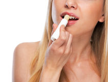 Closeup on happy teenage girl applying hygienic lipstick. Isolated on white royalty free stock photography