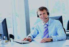 Happy young man working at callcenter, using headset. Closeup Of Happy Telephone Operators Royalty Free Stock Photography