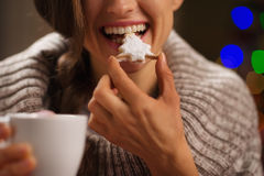 Closeup on happy woman eating Christmas cookie Royalty Free Stock Image