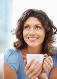 Closeup of a happy woman holding a coffee cup Royalty Free Stock Image