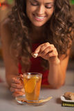 Closeup on happy woman putting brown sugar cube into ginger tea Stock Photography