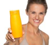 Closeup on happy woman showing sun screen bottle Stock Photo