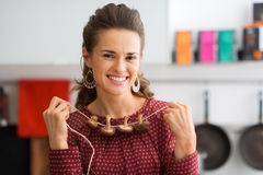 Closeup of happy woman stringing mushrooms together in kitchen Royalty Free Stock Photography