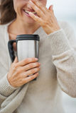 Closeup on happy woman in sweater on beach with cup of beverage Royalty Free Stock Photo