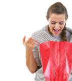 Closeup on happy woman in sweater looking in shopping bag Stock Image