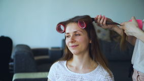 Closeup of happy women friends make fun curler hairstyle each other and have fun. At home stock footage