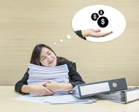 Closeup happy working woman sleeping with happy face after she finish her work and good dream to receive money with work paper in. Front of her on wood desk and Royalty Free Stock Images
